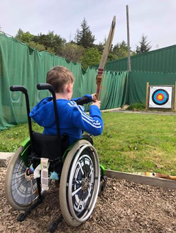 Young person shooting a bow into a target, he's wearing a blue hoody and sitting in a manually propelled wheelchair holding an arrow and bow.